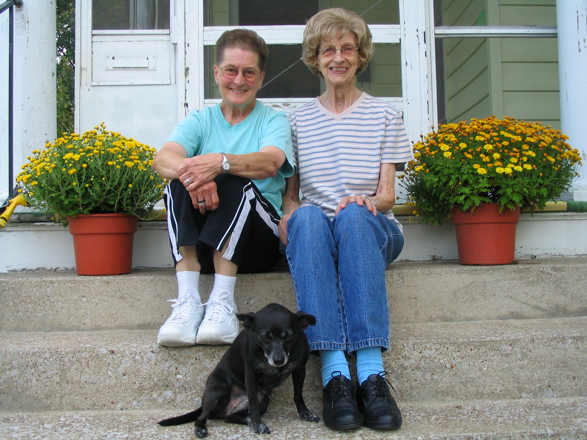 Sr. Jeanette and Sr. Mary Carolyn sitting on the front steps of their house.